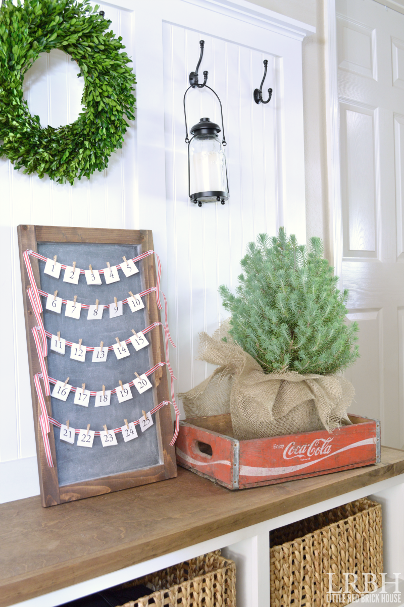 chalkboard advent calendar sitting on mudroom bench next to mini christmas tree